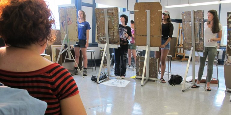 Teens drawing model at easel